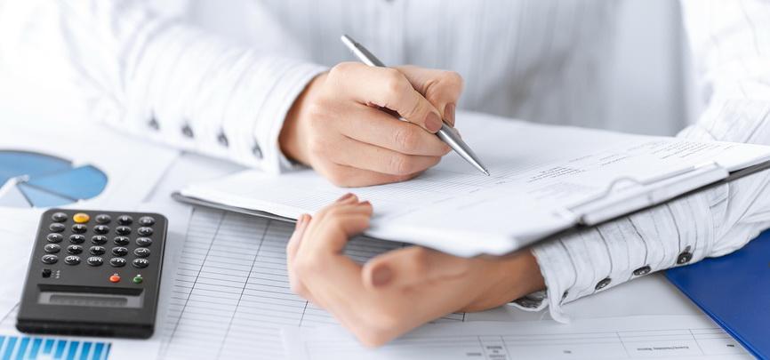Молодая женщина работает за столом с деловыми бумагами